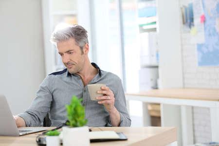 operarios trabajando: Hombre Relaxed que trabaja de forma como local en la computadora portátil