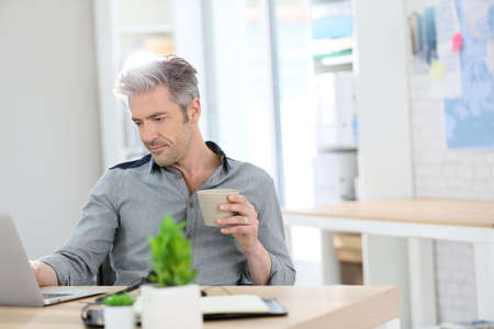 Relaxed man working form home on laptop Standard-Bild