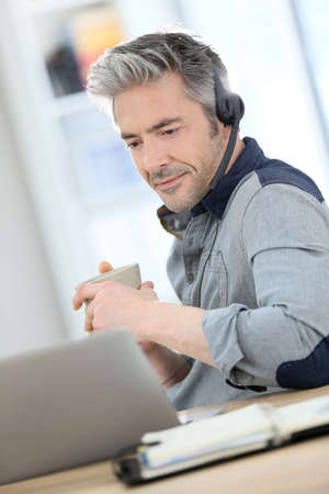 phonecall: Mature man teleworking from home with laptop Stock Photo