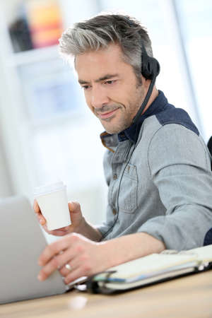 teleworking: Mature man teleworking from home with laptop Stock Photo
