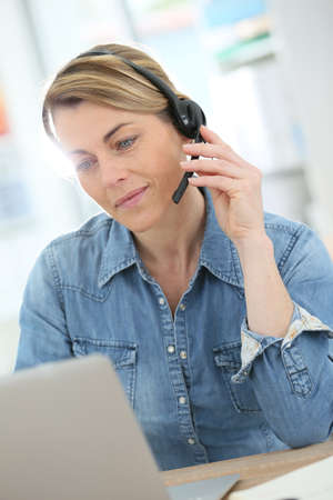 phonecall: Active woman teleworking from home Stock Photo