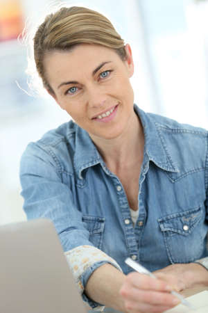 telework: Businesswoman working from home on laptop