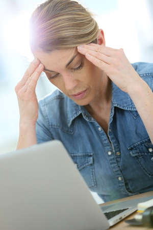 dolor de cabeza: Mujer delante de la computadora portátil sufrimiento el dolor de cabeza Foto de archivo
