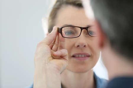 eye exam: Mature blond woman with optician trying eyeglasses Stock Photo