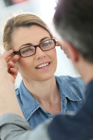 optician: Mature blond woman with optician trying eyeglasses Stock Photo