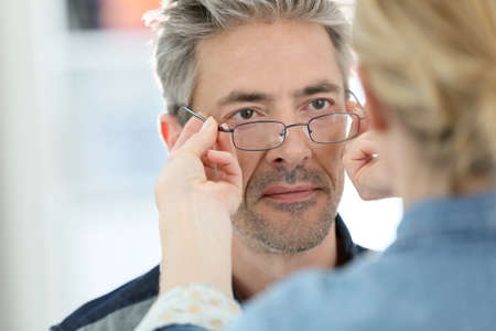 Mature man in optical store trying eyeglasses on Stock Photo