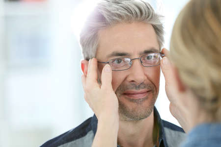 Mature man in optical store trying eyeglasses on photo