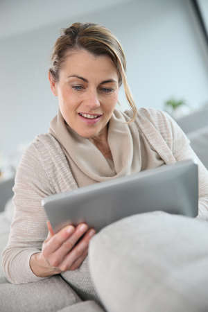 websurfing: Mature woman sitting in sofa and websurfing with tablet