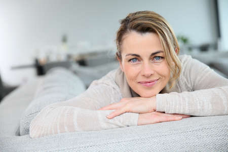 attractive couch: Portrait of mature smiling blond woman