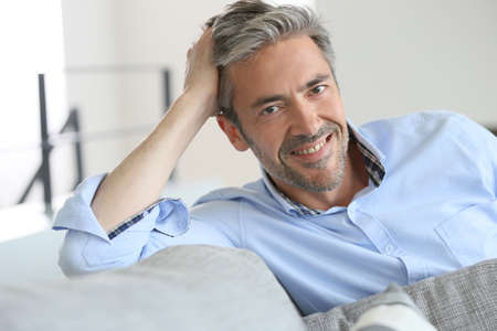 Lachende knappe 45-jarige man ontspannen thuis