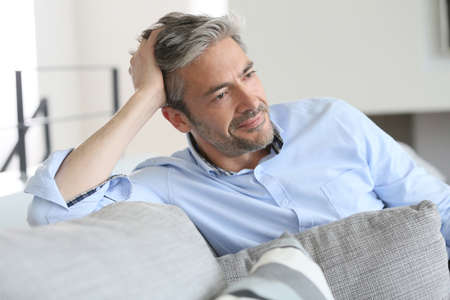 man couch: Smiling handsome 45-year-old man relaxing at home