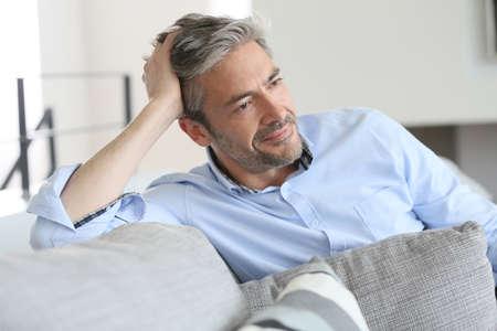 Usmívající se pohledný 45-letý muž relaxační doma