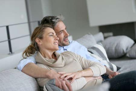 pareja viendo television: Pareja joven sentado en el sofá, mirando a otro lado