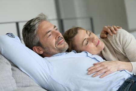 relajado: Pareja joven relajante en el sof�, escena pac�fica