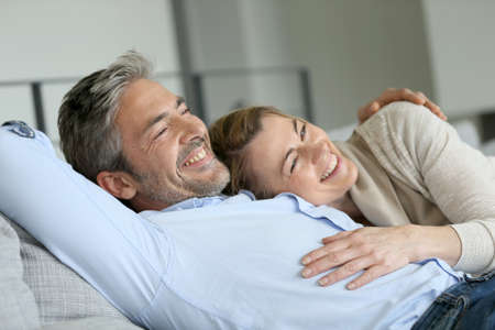 couple couch: Mature couple relaxing in sofa, peaceful scene