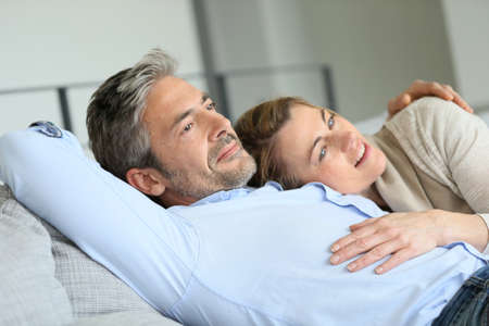 couple on couch: Mature couple relaxing in sofa, peaceful scene