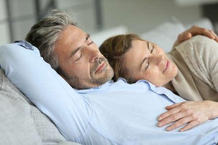 marido y mujer: Pares maduros que tienen un resto que se establecen en el sofá