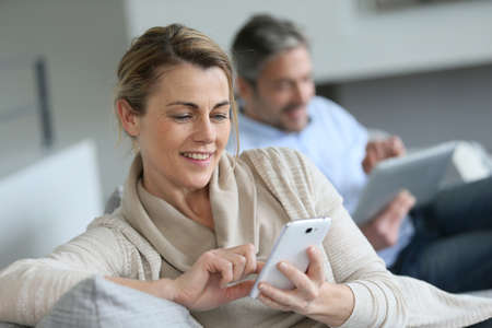 husband: Mature woman using smartphone, husband in background