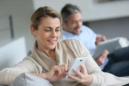 marido y mujer: Mujer madura que usa smartphone, el marido en el fondo