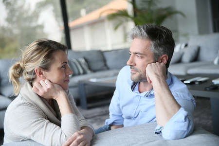 Mature couple talking to each other in sofa Stockfoto