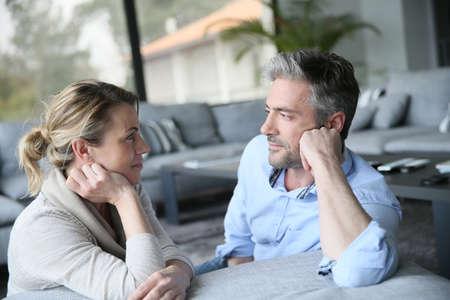 pareja casada: Pareja mayor hablando el uno al otro en el sofá