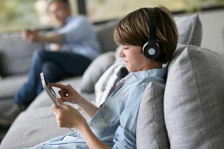 Tenager watching movie on digital tablet with headphones on Фото со стока