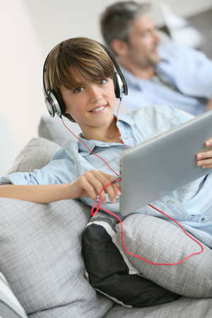 tenager: Tenager watching movie on tablet with headphones on