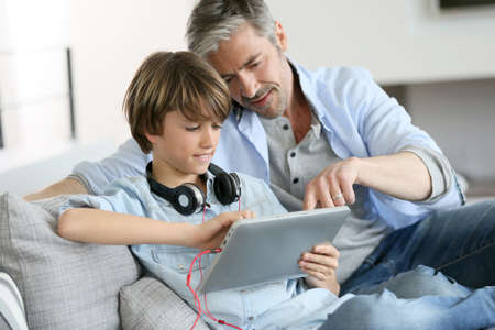 Father watching kid playing with tablet