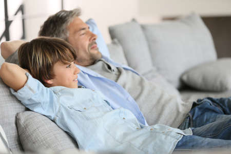 family couch: Father and son relaxing in sofa a thome Stock Photo