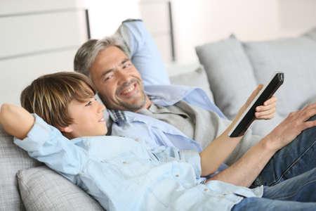 personas mirando: Padre e hijo viendo tv juntos