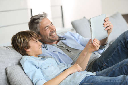 couches: Daddy and son websurfing on digital tablet at home Stock Photo