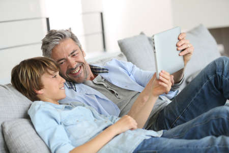 Daddy and son websurfing on digital tablet at home Stock Photo