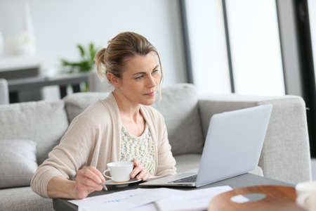 Middle-aged woman working from home on laptop Stock Photo - 38883682