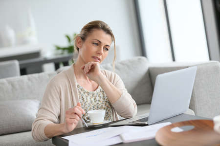 trabjando en casa: Mujer de mediana edad que trabaja desde su casa en la computadora portátil Foto de archivo