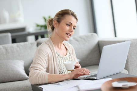 mujeres maduras: Mujer de mediana edad que trabaja desde su casa en la computadora portátil Foto de archivo