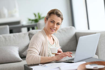 Middle-aged woman working from home on laptop photo
