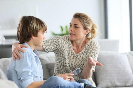 Madre que da el cuidado al muchacho joven con smartphone Foto de archivo - 38883688