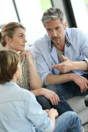 serious: Parents having a talk with teenage boy
