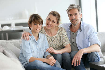 Portrait of happy family of three sitting in sofa at home Stock Photo
