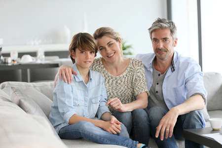 family portrait: Portrait of happy family of three sitting in sofa at home Stock Photo