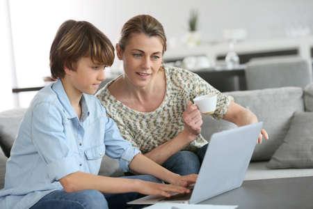 Мать смотрит в честь сына делать домашнее задание на ноутбуке