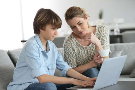looking after: Mother looking after son doing homework on laptop