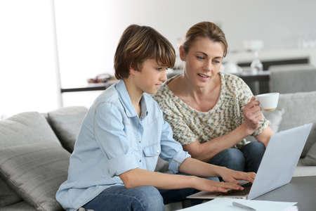 deberes: Madre cuidando de hijo hacer la tarea en la computadora portátil