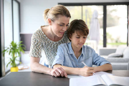 Mother helping kid with homework