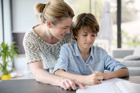 caucasian children: Mother helping kid with homework