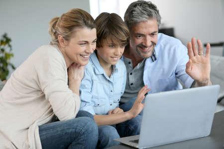 video call: Happy family of three waving at camera during video call Stock Photo