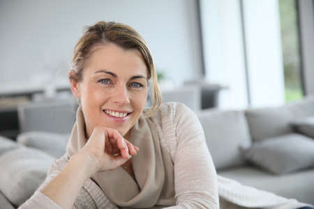 blonde yeux bleus: Portrait de femme mûre de détente dans le canapé