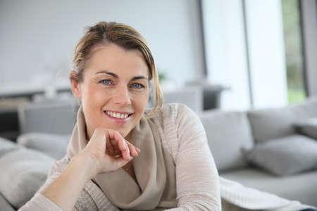 Portret van rijpe vrouw ontspannen in een bank