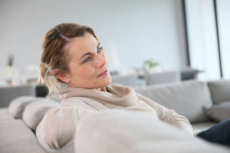 middleaged: Peaceful middle-aged woman sitting in sofa Stock Photo