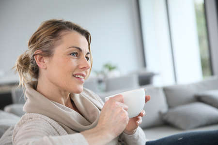 attractive person: Mature woman in sofa drinking hot coffee